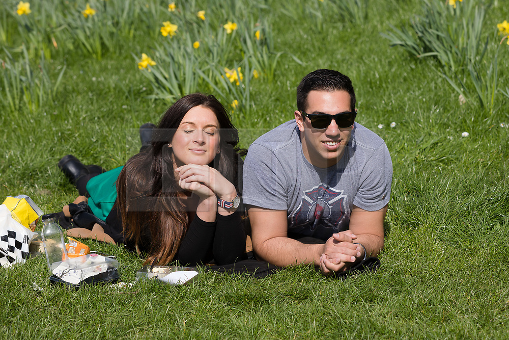 © Licensed to London News Pictures. 26/03/2017. LONDON, UK. A couple relax on the grass during sunny spring weather in Green Park, London this lunchtime. Today is the first day of British Summer Time (BST). Photo credit: Vickie Flores/LNP