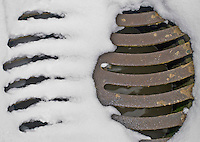 Close-up of a partly snow-covered drain cover.