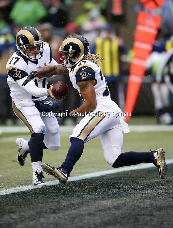 St. Louis Rams running back Tre Mason (27) takes a handoff from St. Louis Rams quarterback Case Keenum (17) as he runs the ball from his own end zone during the 2015 NFL week 16 regular season football game against the Seattle Seahawks on Sunday, Dec. 27, 2015 in Seattle. The Rams won the game 23-17. (©Paul Anthony Spinelli)