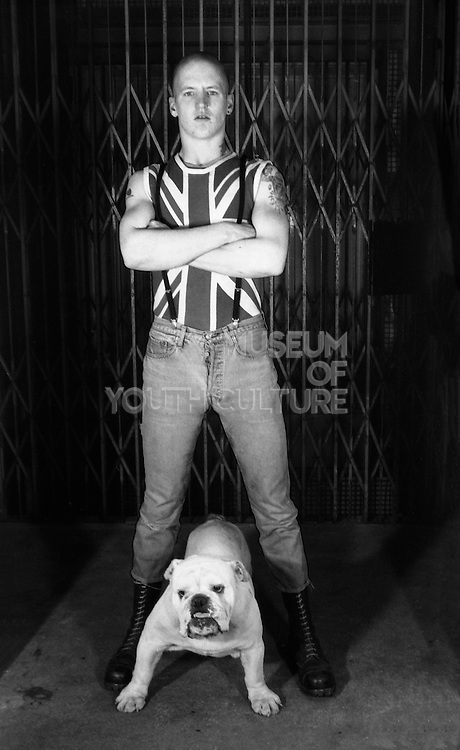 Skinhead man wearing Union Jack shirt with dog, High Wycombe, UK, 1980s.