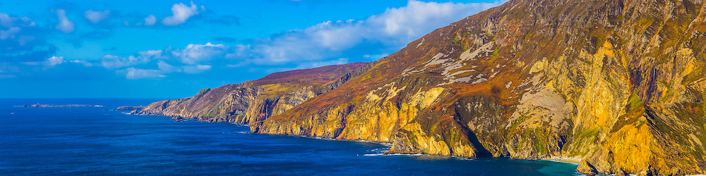 View overlooking the Slieve League Cliffs from Bunglass viewpoint. This one is from my holiday to Donegal back at the end of October 2014. This time the weather was much brighter than when I was last here the year before. With being a similar time of year the orange ferns on the rugged slopes of the cliffs were on show again, with the bright sun giving a much warmer feel to the image. Image composed of 9 photos at 85mm in portrait orientation offering stunning levels of detail, including 3 waterfalls streaming down the rugged slopes, the lighthouse on Rathlin O'Birne Island, the Napoleonic Signal Tower at Malin Beg and even some sheep on the far away slopes near Malin Beg.<br /> <br /> Image composed of 5 photos at 85mm in portrait orientation offering stunning levels of detail. You can zoom in and take a closer look to see what this could look like on your wall here http://adambrooks.photoshelter.com/#!/p/I0000yBXJnJjnQo4<br /> <br /> Available in sizes ranging from 8&quot;x32&quot; - 20&quot;x80&quot; (20cmx81cm - 51cmx203cm).
