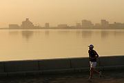 Museum of Islamic Art designed by American star architect I.M. Pei (l.). Jogger at sunrise.