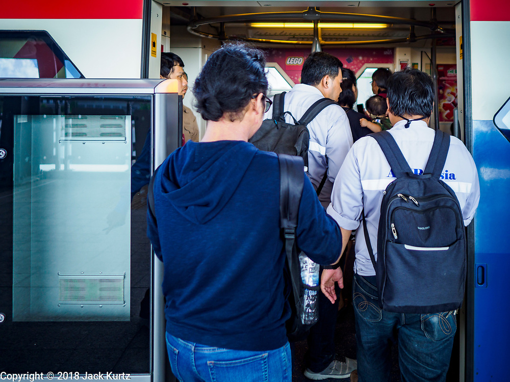 06 DECEMBER 2018 - SAMUT PRAKAN, THAILAND:  People board the BTS Skytrain in Kheha station. The 12.6 kilometer (7.8 miles) east extension of the Sukhumvit Line of the Bangkok BTS Skytrain opened today. The system is now 51 kilometers long (32 miles), including the 12.6 kilometer extension that opened 06 December. About 900,000 people per day use the BTS.       PHOTO BY JACK KURTZ