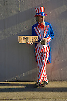 Uncle Sam standing against a wall with a beggars cup and a homeless cardboard sign.