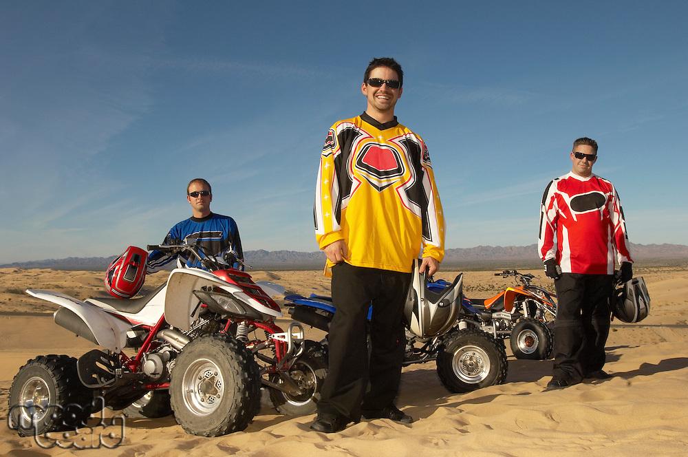 Men standing by quad bikes in desert