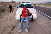 17 MAY 2006 - GILA BEND, AZ: A man arrested by MCSO deputies bows his head while resting on the hood of a patrol car in rural Maricopa county. Deputies from the Maricopa County Sheriff's Department run an anti-smuggling operation along I-8 near Gila Bend, AZ. Deputies arrested 12 illegal immigrants from Mexico during the operation. PHOTO BY JACK KURTZ