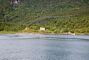 Isolated coastal houses on wooded land near Ornes, Nordland, Norway