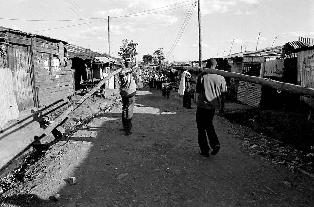 While people from larger tribes hold important positions in the private and public sectors in Kenya, few, if any, Nubians have positions significant enough to help influence their community's development and voice in society.   Most Nubian youth find they are limited to working odd jobs in Kibera. Two Nubian young men carry bamboo logs to another section of Kibera. It is the only job they can secure for the day. They are paid 40 Kenya Shillings each (.75 USD) for the job.