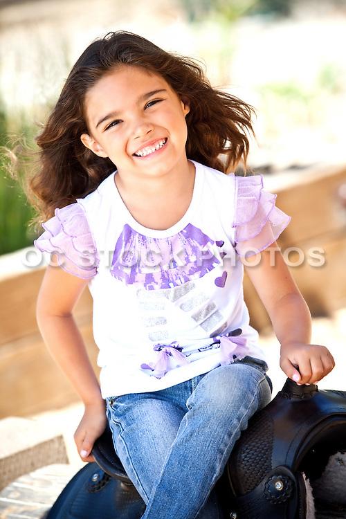 Cute And  Smiling Hispanic Girl Sitting On A Saddle