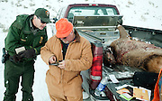 PRICE CHAMBERS / NEWS&amp;GUIDE<br /> Rick Coy shows his hunting license to Grand Teton National Park ranger Chris Harder on Sunday along the Gros Ventre Road.
