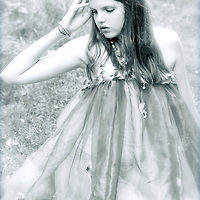 A young girl alone kneeling on grass holding a hand to her head