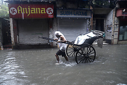 July 24, 2017 - Kolkata, West Bengal, India - A Rickshaw puller wades  through a road flooded by heavy rain.  (Credit Image: © Saikat Paul/Pacific Press via ZUMA Wire)