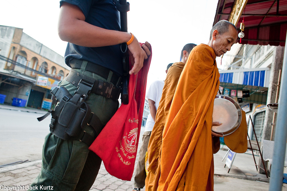 "Sept. 25, 2009 -- PATTANI, THAILAND: Soldiers and police officers accompany Buddhist monks on their morning rounds soliciting alms in Pattani, Thailand. Monks have been the targets of Muslim insurgent assassins who kill representatives of Thai Buddhist culture include monks and teachers. Thailand's three southern most provinces; Yala, Pattani and Narathiwat are often called ""restive"" and a decades long Muslim insurgency has gained traction recently. Nearly 4,000 people have been killed since 2004. The three southern provinces are under emergency control and there are more than 60,000 Thai military, police and paramilitary militia forces trying to keep the peace battling insurgents who favor car bombs and assassination.  Photo by Jack Kurtz"
