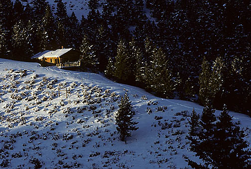 Log cabin nestled in the Bridger mountains, snow covers slopes. Montana.