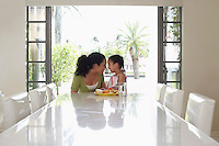 Mother and daughter (5-6 years) sitting at dining table