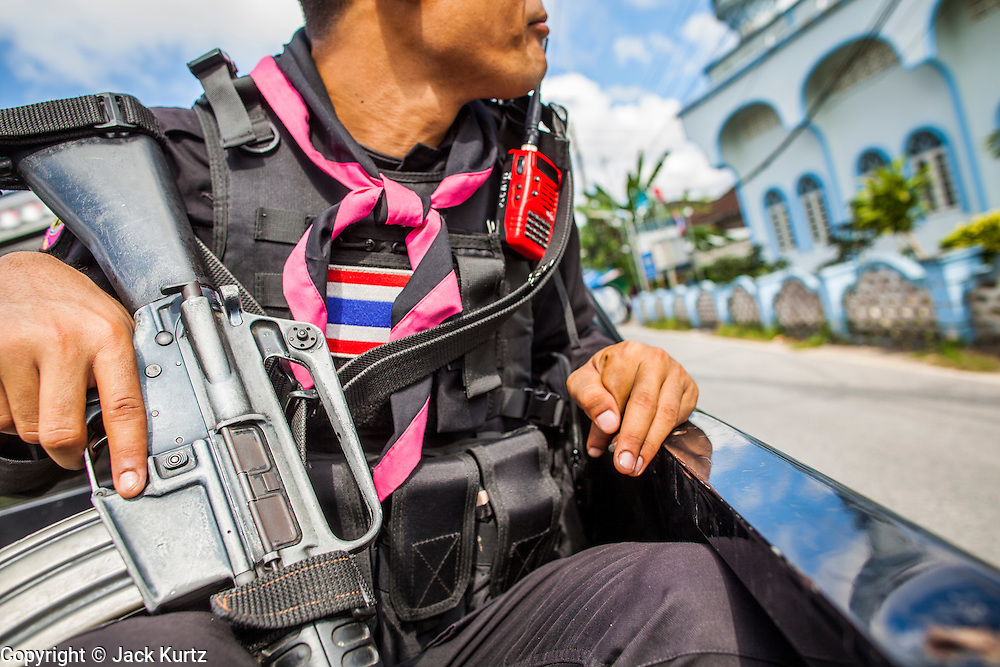 31 OCTOBER 2012 - YARANG, PATTANI, THAILAND:  A Thai soldier on the Wat Kohwai security detail looks at a mosque the procession passed enroute Yala for Ok Phansa. Ok Phansa marks the end of the Buddhist 'Lent' and falls on the full moon of the eleventh lunar month (October). It's a day of joyful celebration and merit-making. For the members of Wat Kohwai, in Yarang District of Pattani, it was a even more special because it was the first time in eight years they've been able to celebrate Ok Phansa. The Buddhist community is surrounded by Muslim villages and it's been too dangerous to hold the boisterous celebration because of the Muslim insurgency that is very active in this area. This the year the Thai army sent a special group of soldiers to secure the village and accompany the villagers on their procession to Yala, a city  about 20 miles away.  PHOTO BY JACK KURTZ