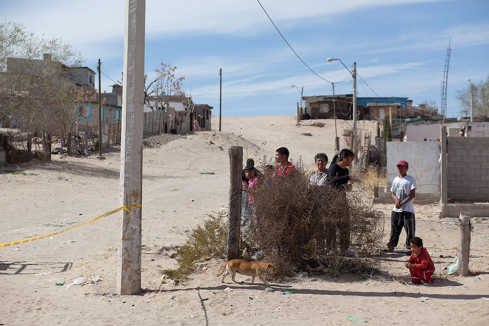 People look on at a crime scene in Anapra.