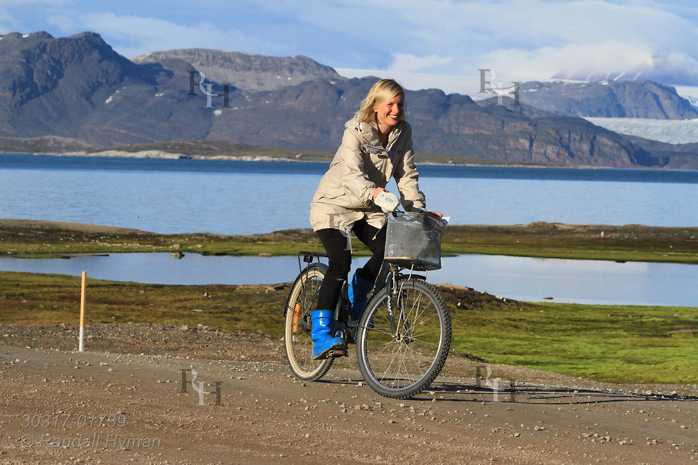 Woman rides bicycle along shores of Kongsfjorden at the international science village of Ny-Alesund on Spitsbergen island, Svalbard, Norway.