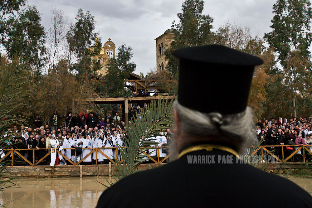 QASR AL YAHUD, WEST BANK - JANUARY 18: A Greek Orthodox priest look over into Jordan where christian pilgrims gather on the banks of the River Jordan during Epiphany celebrations on January 18, 2010 at the Qasr al Yahud baptism site, near Jericho, West Bank. Hundreds of Orthodox pilgrims gathered at the site where according to Christian tradition John baptized Jesus in the waters of the river. (Photo by Warrick Page)