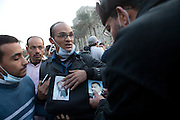 Egyptian man Mohamed Umran ,25, a lawyer , argues with a man who disputes his photographs of Bin Laden and former Egyptain President Gamel Abdu Nasser , the Egyptian President in the 1950's and 60's . Umran claims that everyone in Egypt now hates America for their involvement in Egyptian politics and supply of weapons, such as tear gas which is being used against the protestors . (Photo by Heidi Levine/Sipa Press).