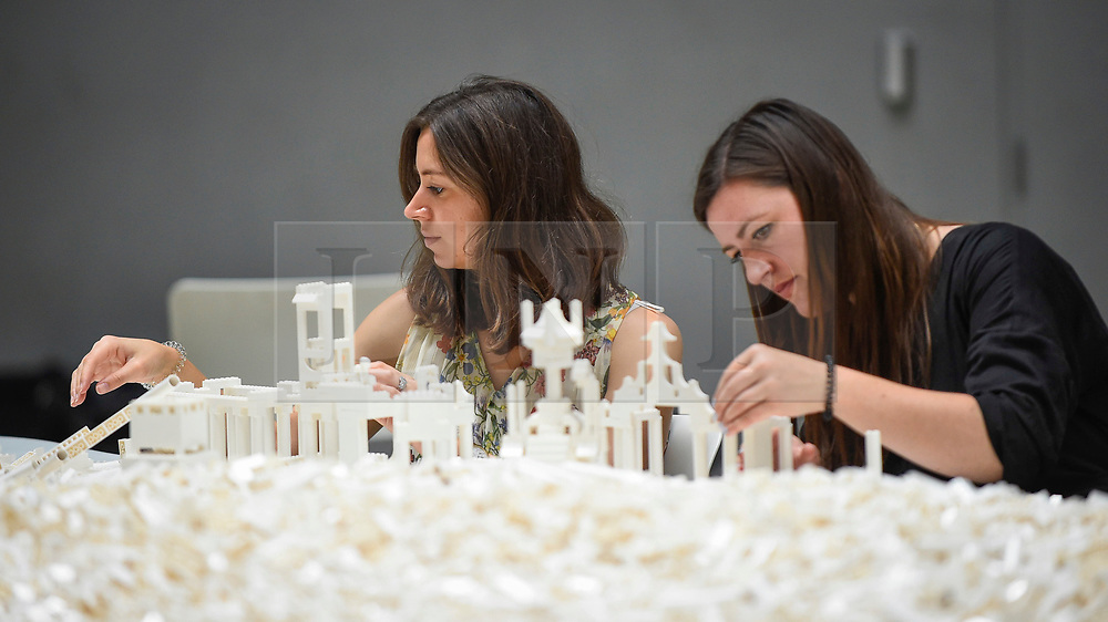 "© Licensed to London News Pictures. 26/07/2019. LONDON, UK. Visitors work with Lego at the preview of ""The cubic structural evolution project"", 2004, by Olafur Eliasson at Tate Modern.  Exhibited for the first time in the UK, the artwork comprises one tonne of white Lego bricks inspiring visitors to create their own architectural vision for a future city and is on display until 18 August 2019.  The work coincides with the artist's new retrospective exhibition ""In real life"" at Tate Modern on display to 5 January 2020.  Photo credit: Stephen Chung/LNP"