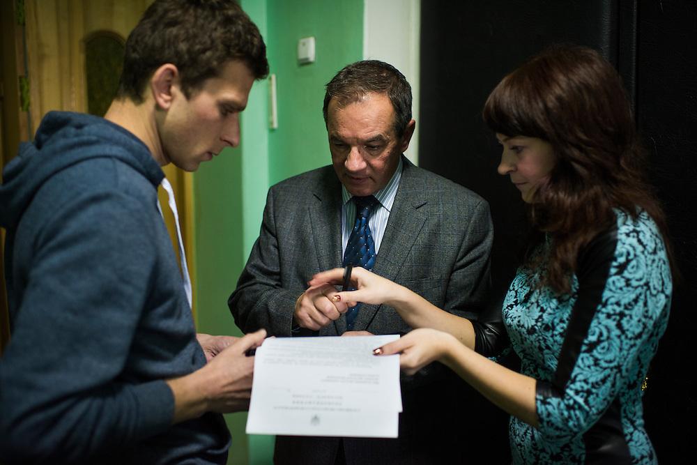 Michel Terestchenko signe des papiers pr&eacute;par&eacute;e par Alyona Demicheva, &agrave; droite, son ancienne collaboratrice &agrave; Linen of Desna, d&eacute;sormais secr&eacute;taire de la mairie dans la mairie le 7 d&eacute;cembre 2015 &agrave; Hlukhiv, Ukraine.<br /> <br /> Michel Terestchenko signs papers prepared by his assistant, Alyona, right, as he leaves his office on December 7, 2015 in Hlukhiv, Ukraine.