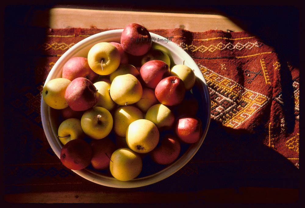 Red and yellow apples in a bowl on a Turkish djijim..Red and yellow apples in a bowl on a Turkish djijim.