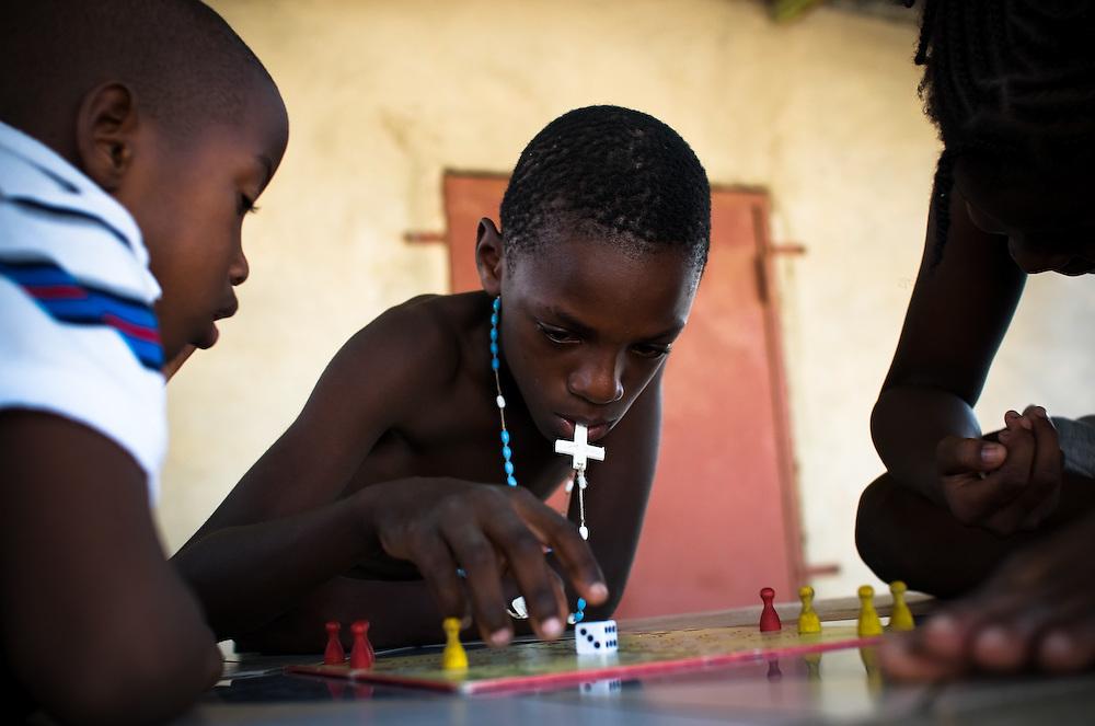 Children play a board game and speak Papiamentu in Buena Vista, a slum in Willemstad, Curaçao.