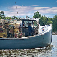 Modern day young lobster man, heading out to set his traps in the Penobscot Bay, central coast of Maine. It's summertime and the weather is warm, so just a light jacket.