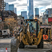 Saveway Construction Enterprises operator of John Deere Construction Excavator tractor  lifting steel road covering plate so crew can  dig up street for replacement of new gas pipes in Waverly Place,  Greenwich Village, NYC. <br /> <br /> Nearly every utility or road construction project requires steel plates or mats to temporarily cover the open excavation and allow for vehicle and pedestrian traffic over the excavation. <br /> Public officials and engineers have long warned about the dangers posed by the outdated, moldering pipelines that snake beneath the streets of major cities like New York, feeding gas into the furnaces of millions of homes.<br /> <br /> For nearly two decades, federal authorities have directed pipeline operators to replace these leak-prone, cast-iron lines with pipes made of plastic and other modern materials. And many states, including New York, have embarked on programs to do just that.<br /> <br /> But these efforts could take decades to complete, and in the meantime, weakened pipes could spring deadly leaks.<br /> <br /> This possibility and the need for repairs have come into sharp focus in the aftermath of an explosion that tore apart two buildings in Manhattan one morning, killing at least seven people and injuring dozens more.<br /> <br /> Pipe layer pipe fitting or pipe fitting is the occupation of installing or repairing piping or tubing systems that convey liquid, gas, and occasionally solid materials. This work involves selecting and preparing pipe or tubing, joining it together by various means, and the location and repair of leaks.
