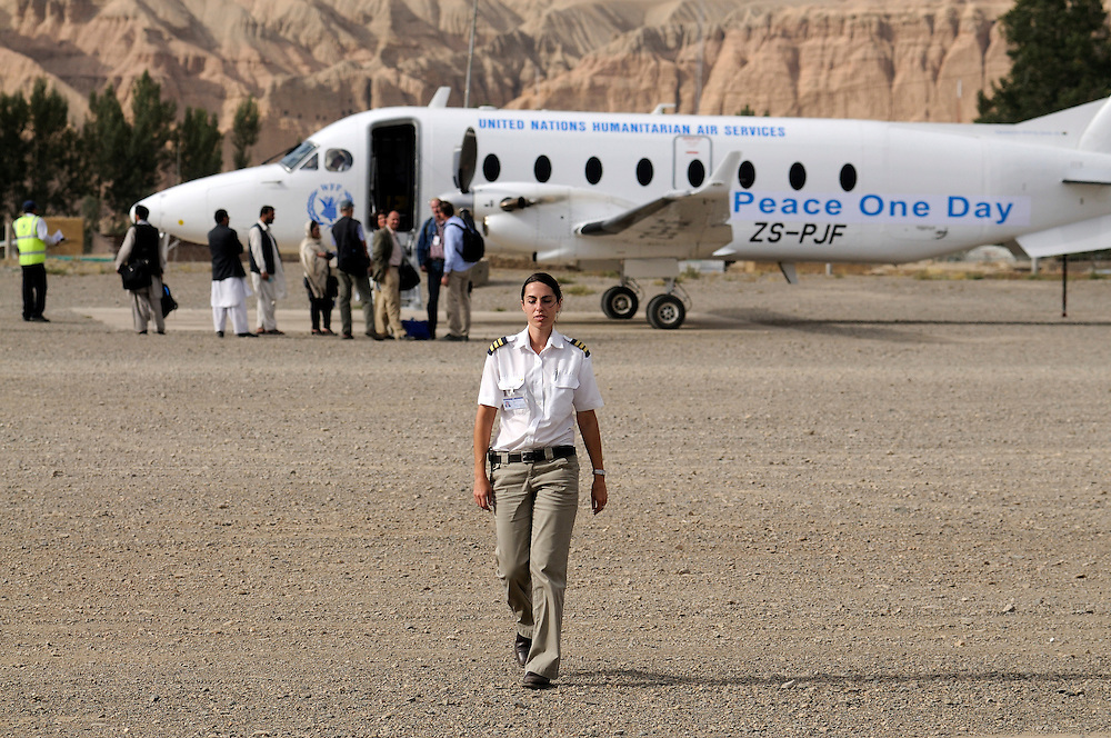 Pilot, Danielle Aitchison, walks accross the Bamiyan airstrip, while passengers wait to board the UNHAS flight on the remote Bamiyan air field.  The airstrip is made of rocks and gravel and not entirely straight, making take off and landings more challenging in the remote mountins...