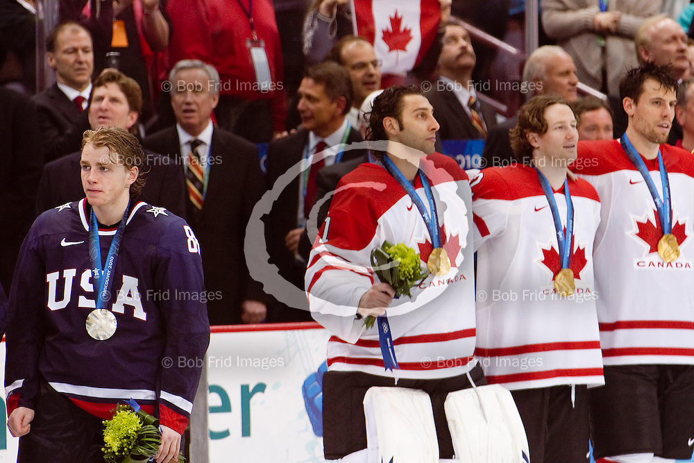 28 February 2010: A deflated silver medalist USA's Patrick Kane #88 stands quietly as the gold medalists from Canada  goalie Roberto Luongo #1, Duncan Keith #2, and Shea Weber #6 sing the Canadian national anthem at the end of the Gold medal Hockey Final between the United States and Canada during the Vancouver 2010 Winter Olympics  in Vancouver,  British Columbia, Canada.  Final score in Overtime: Canada 3 - USA 2 - Canada wins the Gold Medal and the USA Silver.