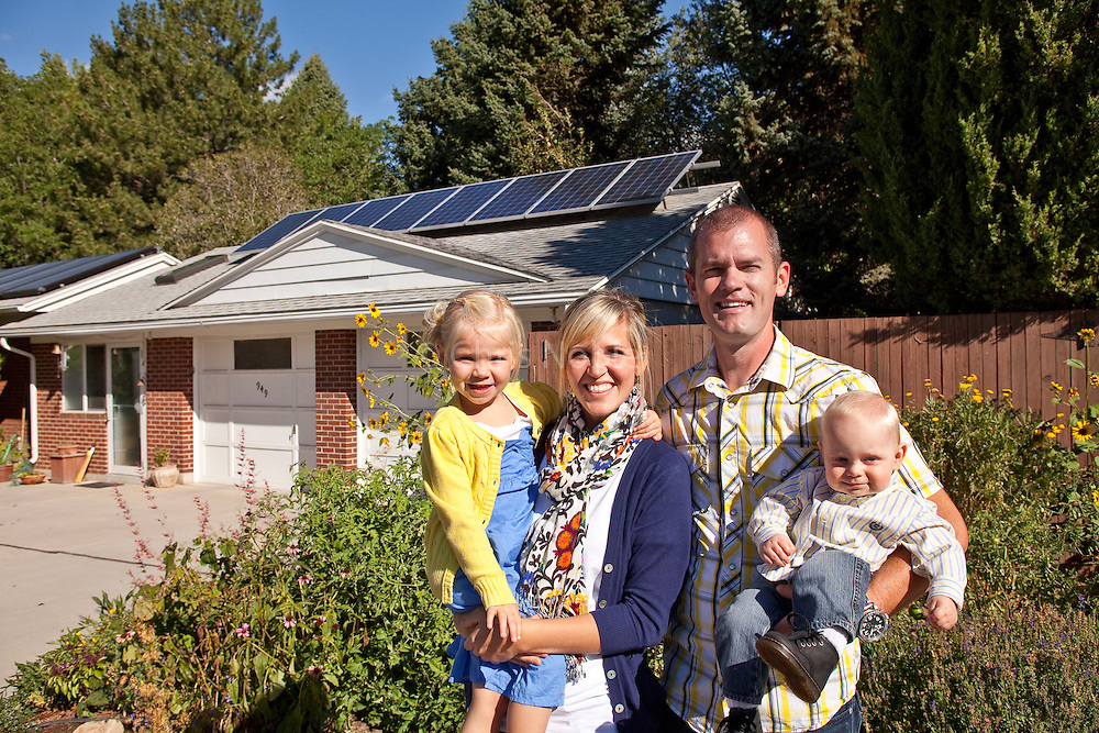 A young family stands proudly before new photovoltaic cells on their soloar powered home.