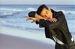 Mime in denim jacket pretending to be resting at the beach