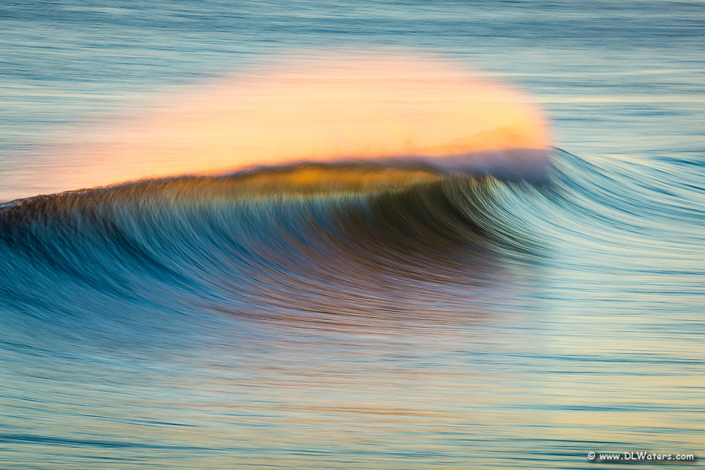 Sunrise windblown surf spray at Kitty Hawk Pier photographed with a long telephoto lens and a slow shutter speed.