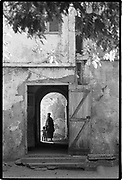 A woman with her child enters her colonial style home on Gor&eacute;e Island, one of the centers for slave trade in West Africa. Visitors go there to tour the slave museum, a memorial to the atrocities of the slave trade. <br />