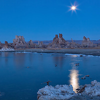 Full moon rises above tufas and calm waters of Mono Lake, near Lee Vining, California