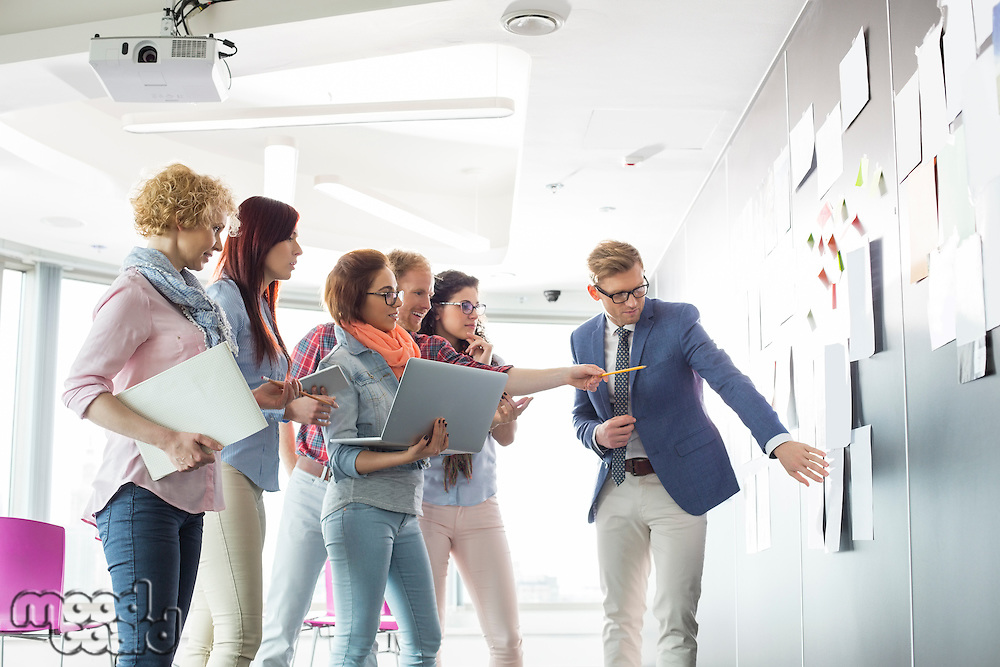 Creative businesspeople discussing over documents on wall in office