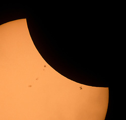 The International Space Station, with a crew of six onboard, is seen in silhouette as it transits the Sun at roughly five miles per second during a partial solar eclipse, Monday, Aug. 21, 2017 near Banner, Wyoming.  Onboard as part of Expedition 52 are: NASA astronauts Peggy Whitson, Jack Fischer, and Randy Bresnik; Russian cosmonauts Fyodor Yurchikhin and Sergey Ryazanskiy; and ESA (European Space Agency) astronaut Paolo Nespoli. A total solar eclipse swept across a narrow portion of the contiguous United States from Lincoln Beach, Oregon to Charleston, South Carolina. A partial solar eclipse was visible across the entire North American continent along with parts of South America, Africa, and Europe.  Photo Credit: (NASA/Joel Kowsky)
