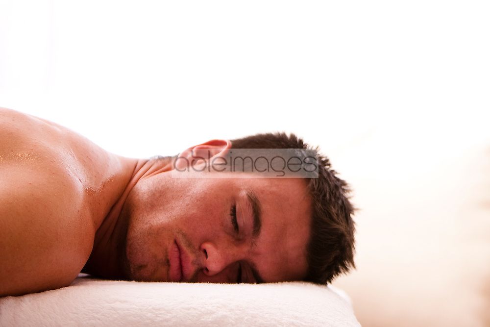 Close up profile of a man lying on a treatment bench with his eyes closed