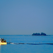 Lobster boat steaming at sunset on Penobscot Bay. Stonington, Maine