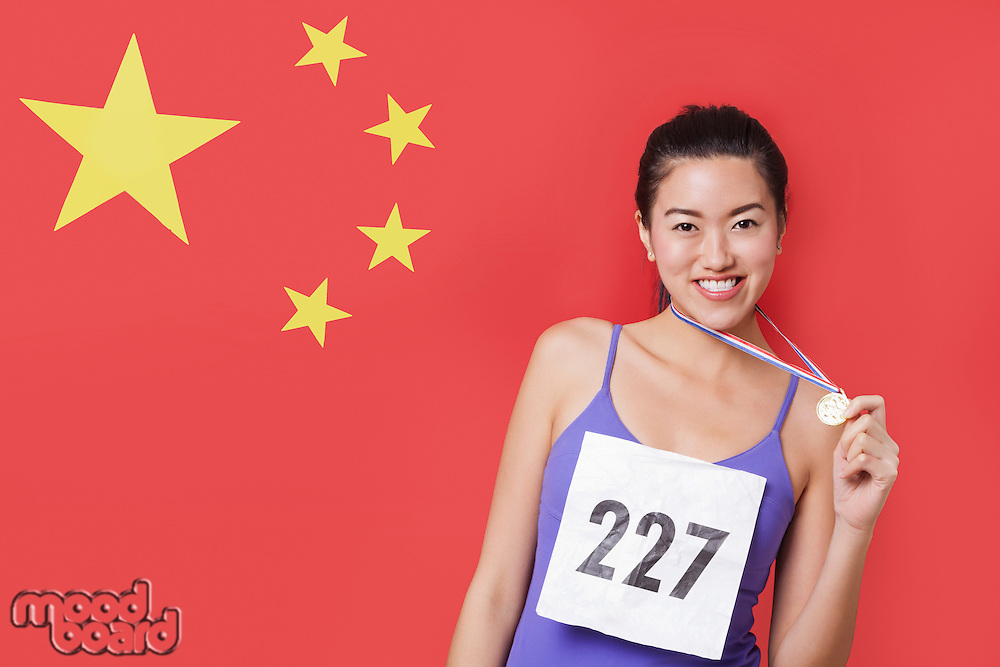 Portrait of smiling young female medalist standing against Chinese flag