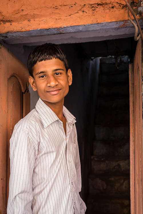 The portrait of a teenage boy at the door to his home in the Pink City, Jaipur