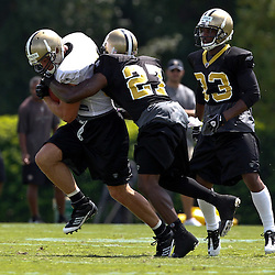 July 29, 2011; Metairie, LA, USA; New Orleans Saints tight end Tyler Lorenzen (82) is wrapped up by cornerback Malcolm Jenkins (27) as cornerback Jabari Greer (33) pursues during the first day of training camp at the New Orleans Saints practice facility. Mandatory Credit: Derick E. Hingle