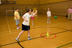 Group of Day service user with learning disability playing indoor cricket in the gym