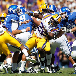 October 1, 2011; Baton Rouge, LA, USA;  Kentucky Wildcats quarterback Maxwell Smith (11) has the football stripped by LSU Tigers defenders during the third quarter at Tiger Stadium. LSU defeated Kentucky 35-7. Mandatory Credit: Derick E. Hingle-US PRESSWIRE / © Derick E. Hingle 2011