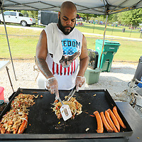 Food vendor Landrick Jones, from Byhalia, cooks up some Jamaican Jerk Sausage at his food stand during Picnic in the Park At Ballar Park Wednesday afternoon in Tupelo.