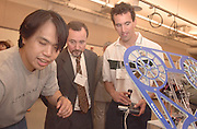 Yong Liu, PHD Student in electrical Engineering demonstates a Test Bed for Flight control. IN Back are Ernesto Casstagnet and David Juedes,Electrical Engineering And Computer Science