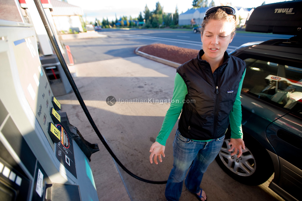 A young woman looking upset at the cost of gas while filling her car. (releasecode: jk_mr1032) (Model Released)