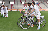German Soccer Bundesliga 2015/16 - Photocall of FC Augsburg on 08 July 2015 in Augsburg, Germany: The players (r-l) Jan Moravek, Caiuby and Ronny Philp pose on electric bikes for sponsorship-pictures, while their teammates meet obligations for other sponsors in the back.
